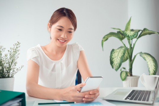 Smiling business lady reading romantic text message