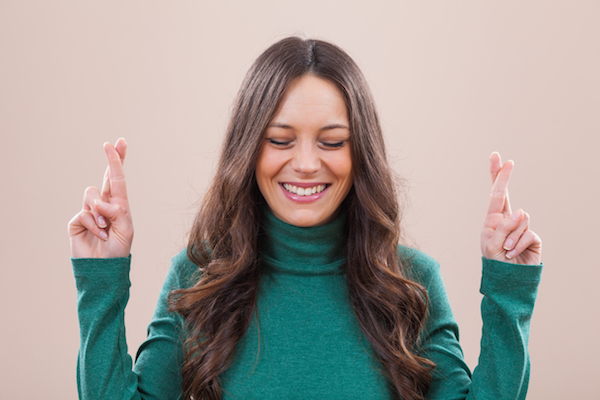 Portrait of happy woman with fingers crossed