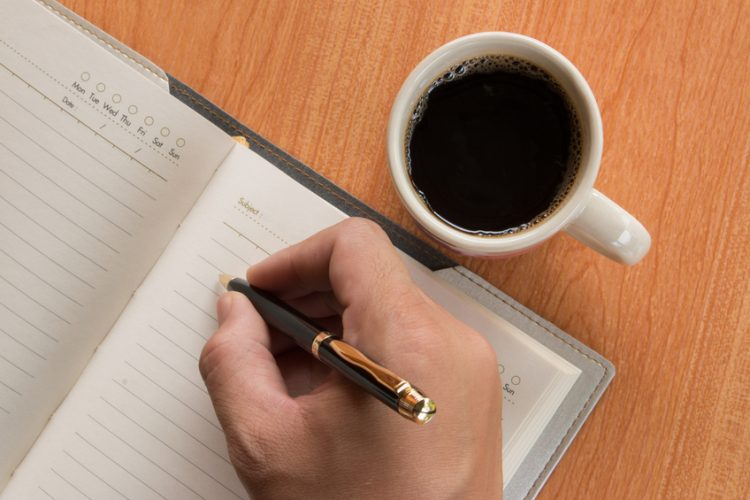 Hand of man writing in open notebook on wooden table with hot coffee