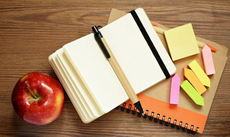 Notebooks, pens, stickers and apple on wooden background