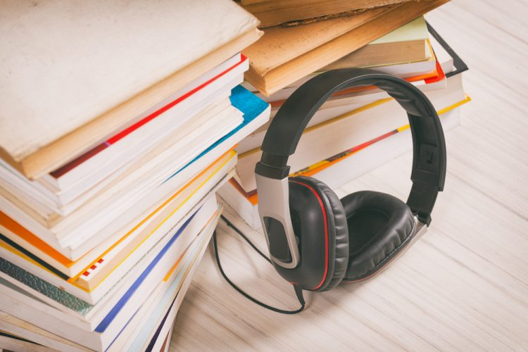 Headphones and the paper books. Concept of listening to audiobooks.